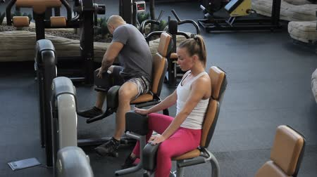 quadriceps : Man and woman doing exercise in machine in gym. Young people sit on seat of iron equipment, choose working weight and with exhalation reduce legs then return to original position. Beautiful couple dressed in stylish sportswear, train intensively, performi Stock Footage