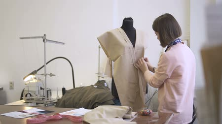 dressmakers model : Young fashion designer is in working process, models clothes on mannequin with cloth, standing in sewing workshop, professional does creative work, fabric and tools are on table. Concept: modeling garment, couture, modern dressmaking. Stock Footage