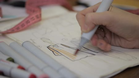 materials : Close up of sketch of dress, which is being colored by fashion designer in the studio. Young woman is applying peach colour to the model on a paper using marker in her hand with golden ring while sitting at the table. Stock Footage