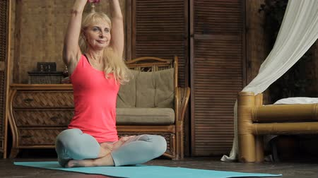 oturum : Mature woman is having yoga training in her vintage bedroom. Blond lady is sitting on blue mat in lotus pose, preparing fot the meditation and doing bharadvaja twist to make her slim body stretch and healthy.