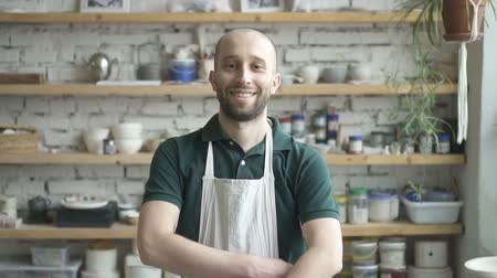 ручная работа : Portrait of male ceramist, who is standing in his studio and watching to the camera, slow motion. Young man in green polo t-shirt and white dickey has beard and smiling. Wooden shelves with colours, tools, dishes and plants are on the backgound.