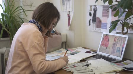 ドレスメーカー : Portrait of female fashion designer, who is drawing drafts in her bright studio. Young lady is sitting at the table with papers, paintings and brand-new laptop on and creating a new models of clothes