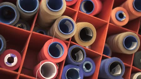 kumaş : Close up of colorful sewing spools in the organizer in design studio. Reels with orange, green, yellow, blue, white threads winding on are lying in the red boxes and waiting for the usage in clothes creation.