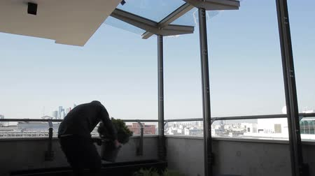 veranda : Male gardener on balcony fluffy flowers are planted in a pot. Man gently transplant green plants in length of container on veranda with views of city. Dostupné videozáznamy