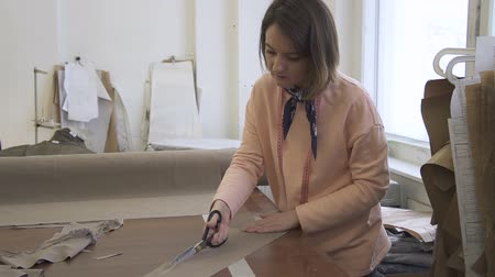 ドレスメーカー : Portrait of female fashion designer, who is cutting the lace from the detail in her studio. Young woman is standing at the wooden table with roll of grey sandy cloth on it and working on the pieces of