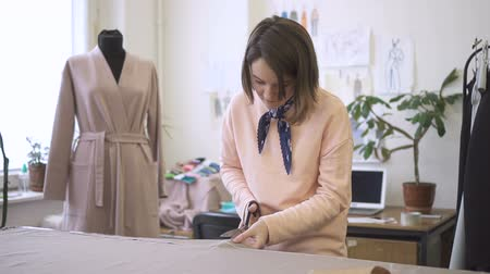 dressmakers model : Portrait of young fashion designer, who is working in her studio. Woman, who wears pink jumper, is standing at the big table with sandy cloth on cutting details by the scissors in her hand. Tropical plants, mannequin, window, desk with brand-new laptop an