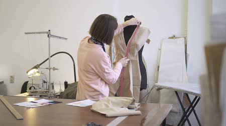 white cloths : Woman tailor takes measurements on fabric on mannequin in atelier. In workplace seamstress measures neckline with a ribbon for sewing female dress. Stock Footage