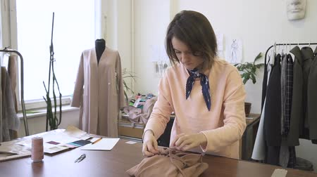 dressmakers model : Portrait of female fashion designer, who is finishing to pack the dress in her studio. Young woman wear pink jumper and blue neckerchief for her work, fastening the laces on the clothes, which is prepared for client. Stock Footage