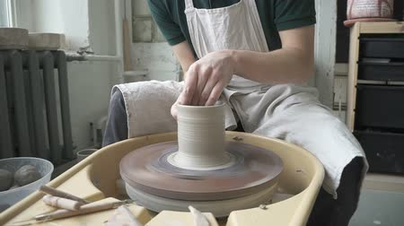 hrnčíř : In pottery workshop man quickly makes high mug with hands on potters wheel. Skilled potter in an apron is sitting and carefully working on making handmade dishes made of clay and water.
