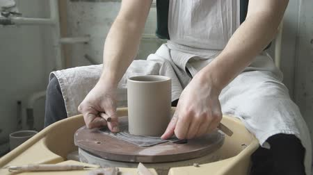 hrnčíř : Close up of mug, which is done in ceramic studio. Male professional in white dickey is sitting at throwing wheel, turning it off, sponging the cup and using rope to cut the bottom fo his creature from the equipment. Ceramist it taking away the tay with di Dostupné videozáznamy