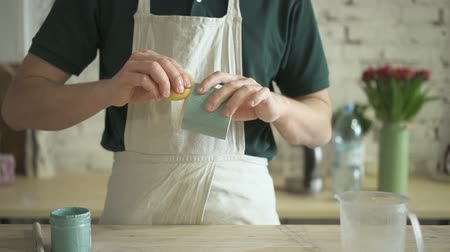 craftsperson : Craftsman with sponge gently erases excess paint from bottom of clay mug. Man in an apron at table cleans edge of finished product from stains in workshop. Stock Footage