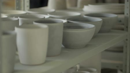 oleiro : Close up of bowls and mugs on the shelf in ceramic studio. White dishes are stanging on stack after applying of enamel, drying and waiting for baking in kiln. This makes creatures prepared to useage. Stock Footage