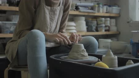 глыба : Artist on potters wheel forms a bowl of lumpy clay. In workshop young and talented artisan with his fingers and tools shapes brown material from moisture and natural soft rock.