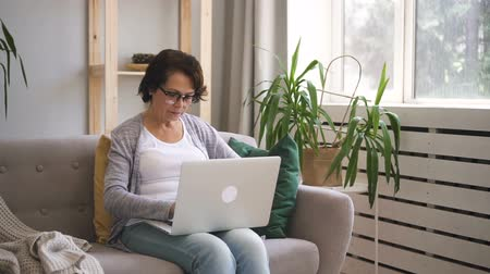 senior lifestyle : Elderly woman is using laptop sitting on sofa at home, seniora wearing glasses is typing, looking at pc screen, having good time near window with green plant in modern interior. Concept: mature person, technology, lifestyle.