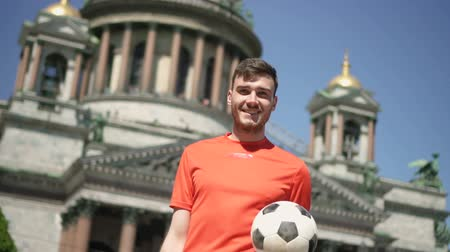 haziran : Young football player moving with ball, posing on background of building in summer, positive bearded guy is training, smiling, having good time on street in sunny day. Concept: training, recreation activity, lifestyle. Stok Video