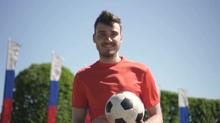 ağaç gövdesi : Young man is holding ball, having good time in city park in summer, russian football player is smiling, posing, looking ahead, standing on background of green trees under blue sky. Concept: successful athlete, good mood, soccer.