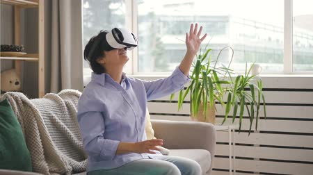 изумление : Elderly woman is using virtual reality glasses, sitting in home interior, happy mature female with modern device on face, having good time, watching 3d movie in apartment. Concept: interactive life, entertainment, cyberspace. Стоковые видеозаписи