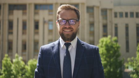 ügyvéd : Confidenr male lawer in glasses, blue suit and tie standing outside and smiling, with court building on the background. Outdoors. Portrait.