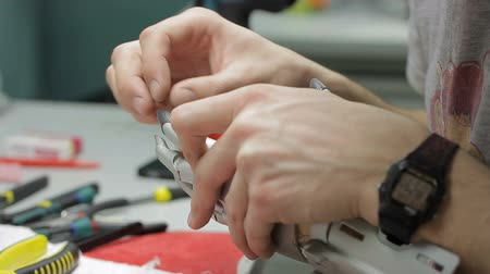 končetina : Young engineer is working with mechanical hand prosthesis in workspace in company, male specialist assembles artificial arm, using tools, sitting at table indoors. Concept: work process, technician job, robotic systems. Dostupné videozáznamy