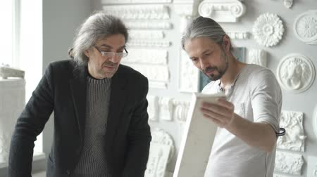 rysunek techniczny : Two mature male interior designers discussing white plaster molding piece in the sculptors studion. Indoors.