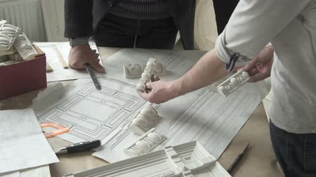 estuque : Hands of male sculprot and architector comparing white plaster molding samples with paper draft on the table in bright studio. Indoors.