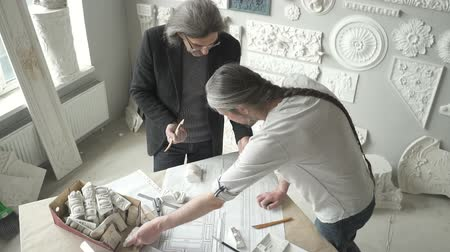 victorian : Two architects restorers are working with creative project standing in bright office, gray haired busy men looking at paper blueprint on table in modern studio with gypsum white elements on wall. Concept: restoring, workshop, architecture.