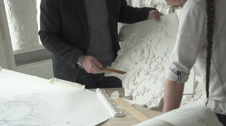 restorer : Experienced architects restorers are working with gypsum decorations in modern workshop, two gray haired men are holding plaster detail, talking about project during work day in bright creative workshop. Concept: designing, vintage decor, workspace. Stock Footage
