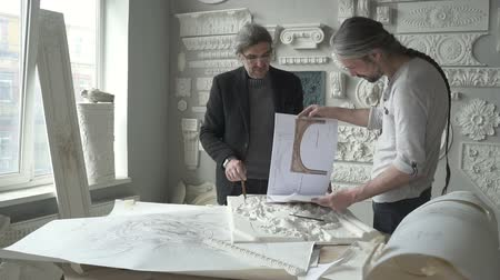 tynk : Two architects restorers are examining restoration project in workspace in bright workshop, talented male masters are working together, looking at colored sketches standing at table in office. Concept: artistic work, tradition, restoring.