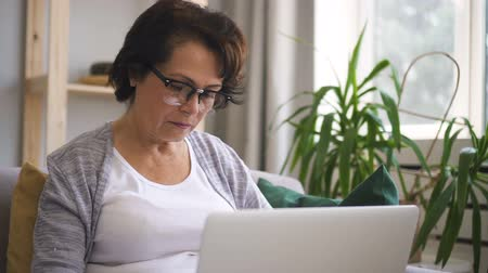 yaşlılar : Mature woman with brown hair, in glasses is sitting at the sofa at home and woking on brand-new laptop. Indoors. Portrait.
