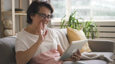věk : Happy mature woman is making video calling using tablet sitting on couch, beautiful female is holding device, talking, looking at screen, smiling on soft sofa in home atmosphere. Concept: communication, social media, friendship