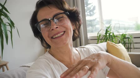 call out : Mature woman in glasses smiling while having video call, talking and showing view from window. Indoors. Portrait. Straight shot. Close up. Stock Footage