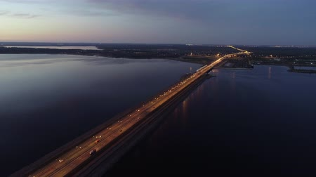 nazomer : Amazing aerial view of bridge and city when sun goes down, beautiful panorama of small city with traffic moving on road, calm river under clear blue sky on late evening in summer. Concept: transportation, landscape, travel. Stockvideo
