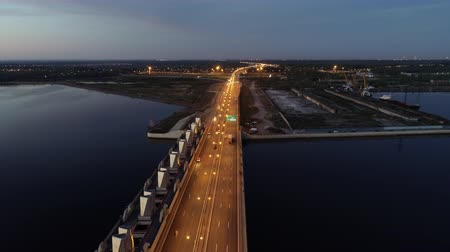 ссылка : Cars moving on highway bridge on the sea directing to the industrial zone, on the sunset. Outdoors. Aerial. Стоковые видеозаписи