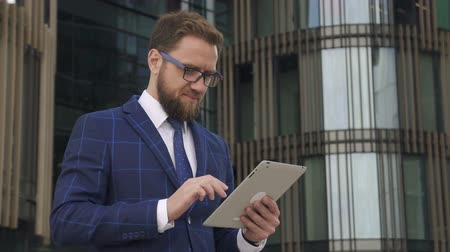 profesyonel meslek : Young confident businessman is using tablet standing on background of company building, rich bearded man wearing glasses is looking at screen with friendly smile during working day in city. Concept: entrepreneur, corporate, lifestyle. Stok Video