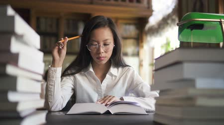 téma : Beautiful woman student is reading book sitting at table in college library, Asian female in white clothes is in educational process, researching topic at desk in vintage interior. Concept: studying, information, lifestyle.
