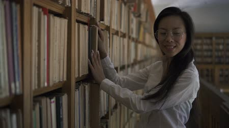 tome : Beautiful asian female student putting the book to the shelf, turning, looking to the camera and smiling. Indoors. Portrait.