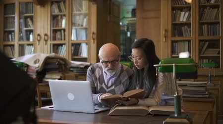 soutien scolaire : Elderly lecturer and young woman discussing theme at table in library, professor and student are talking, looking at book sitting at desk with laptop on background of bookcases. Concept: tutorial, education, vintage interior.