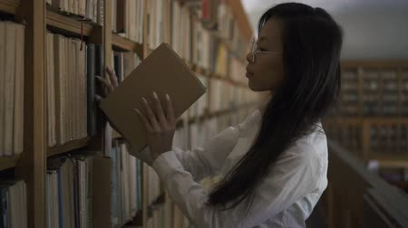 livros didáticos : Young asian woman in round glasses putting the book onto shelf in the library and smiling looking to the camera. Indoors. Portrait.