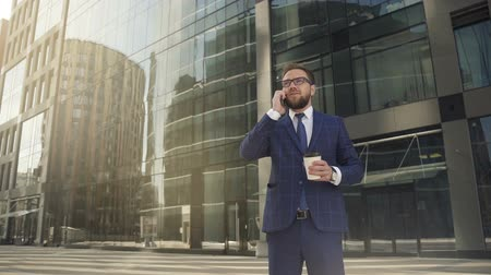 týden : Confident businessman with coffee in hand, talking on phone on metropolis street, bearded man in suit is having conversation about business technology, standing near office building. Concept: business person, working week, career.