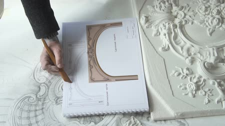 потолок : Close up of plaster molding sample being compared with drawn draft and blueprint by male architect and designer in broght studio. Indoors. Top view.