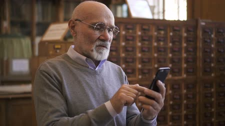 profesor : Respectable professor is using smartphone standing in university library, elderly bearded man is looking at phone screen, typing during working day in reading room. Concept: mature person, lifestyle, messaging. Wideo