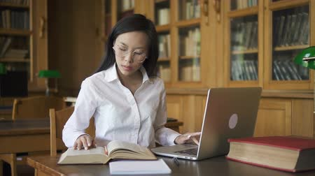 sujeto : Beautiful woman is using laptop, reading book sitting at table in library, young brunette in white shirt is in educational process, researching subject indoors with bookcases. Concept: student, technology, occupation. Archivo de Video