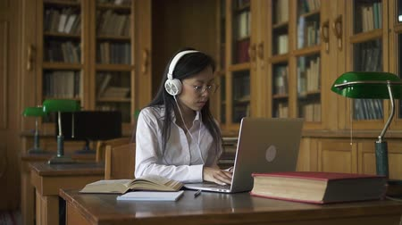 téma : Young beautiful woman studying topic, sitting at table with laptop in library, female in headphones is reading book, looking at pc screen, typing at wooden desk in room with bookcases. Concept: academic, wireless, knowledge.