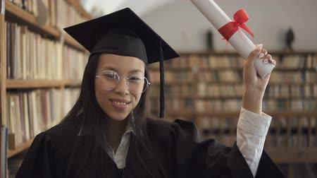 колледж : Smiling female student in academic gown is posing positively standing in library, young woman wearing cap and gown is holding diploma, having fun in university reading room. Concept: graduation, master bachelor, achievement.