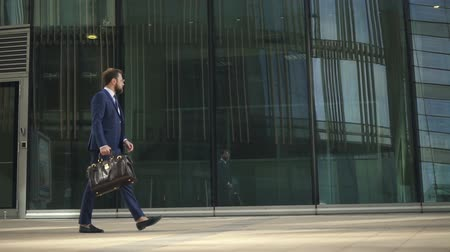 people go to work : Young businessman walking along city street, looking at watch in summer day, successful bearded man with leather bag in hand is going on background of modern building during working day. Concept: business person, millennial, downtown.