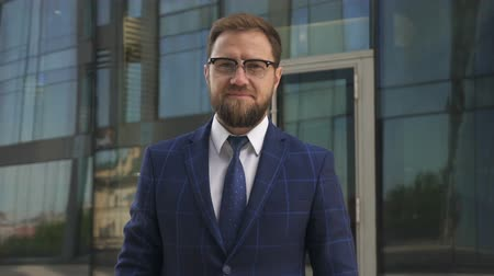 aplicativo : Confinet businessman with beard, in glasses and blue suit taking awat his brand new smartphone, looking to the camera and smiling. Outdoors. Portrait. Stock Footage