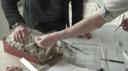 restorer : Architects restorers working with sketches and plaster details at table in modern office, two businessmen are in work process with vintage restoration project and gypsum elements indoors. Concept: restore designing, business people, renovation. Stock Footage