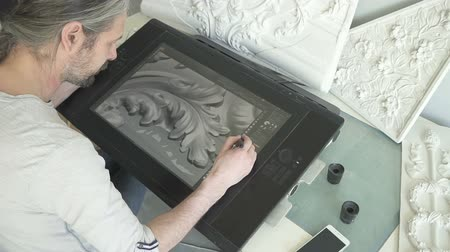 área de trabalho : Mature male artist drawing 3d model of molding with floral ornaments on big graphic tablet in his studio. Portrait. Top back view.
