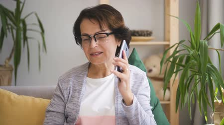 semana : Charming mature businesswoman is using smartphone, making mobile calling in home interior, happy lady is holding phone, talking with smile, sitting on couch in modern apartment. Concept: conversation, modern business, work week.