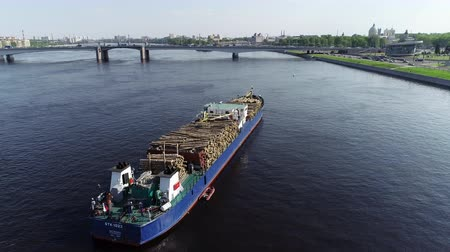 týden : Large boat with wooden load is on river in port city, motionless ship with timber cargo is on calm waters in town with bridge under open blue sky on sunny day. Concept: modern industry, wood export, commercial.